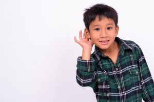 Boy miming hearing against a white background