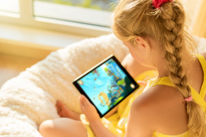girl playing games on tablet