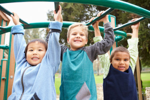 Three young boys climbing on a jungle gym and smiling.
