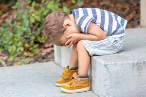 Sad little boy sitting on a step covering his face with his hands.