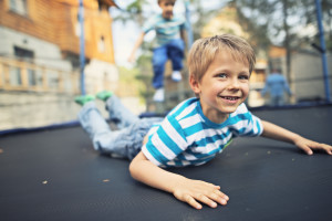 Little boys aged 5 having fun on garden trampoline. First boy is smiling at the camera lying on front and the second boy is jumping in the background.