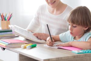 Boy focusing on homework while sitting with mother at desk with notebook and colored pens.