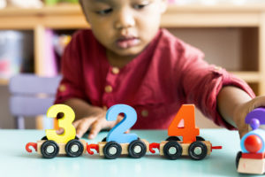 Little boy playing with wooden toys shaped like the number three, two and four.