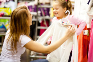 A mother holding a long sleeved shirt on a hanger up against her smiling daughter in a children's clothing store.