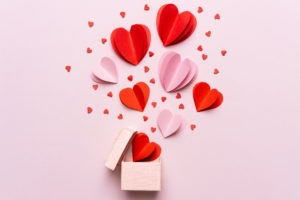 Valentine's day illustration showing red and pink paper hearts bursting upward out of a small box.
