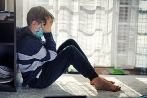 A young boy sits with his back against a wall and cradles his head in both of his hands. He's wearing a blue medical face mask.