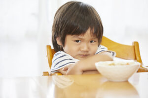A small boy sits at a table with his arms folded, refusing to eat a bowl of food in front of him.