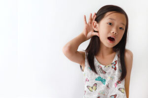 A little girl with long dark hair and a top with butterflies on it cups her right hand behind her right ear, signaling that she has trouble hearing.